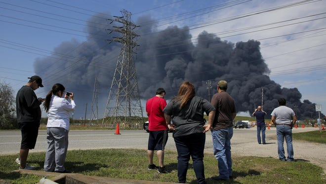 People watch as firefighters continue to battle the fire at Intercontinental Terminals Company on Tuesday.