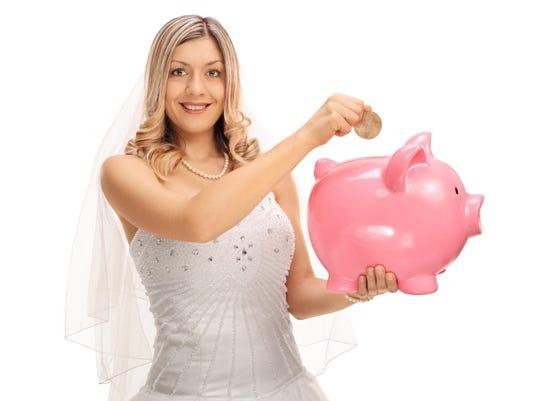 Young bride putting a coin into a piggybank