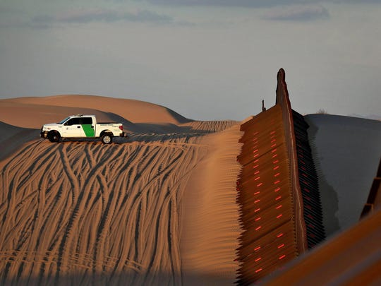 FILE - In this July 18, 2018 file photo, a U.S. Customs and Border Patrol agent patrols a section of floating fence at sunset that runs through Imperial Sand Dunes along the international border with Mexico in Imperial County, Calif. President Donald Trump is not giving up on his demands for $5.7 billion to build a wall along the U.S.-Mexico border, saying a physical barrier is central to any strategy for addressing the security and humanitarian crisis at the southern border. Democrats argue that funding the construction of a steel barrier along roughly 234 miles will not solve the problems. (AP Photo/Matt York, File)