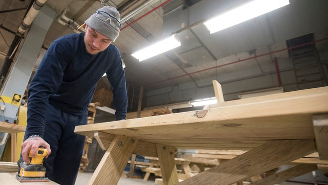 David Moore sands the seat of one of the 16 picnic tables that he and other Ross Correctional Institution inmates have been working on for the Aesop's Tables fundraiser.
