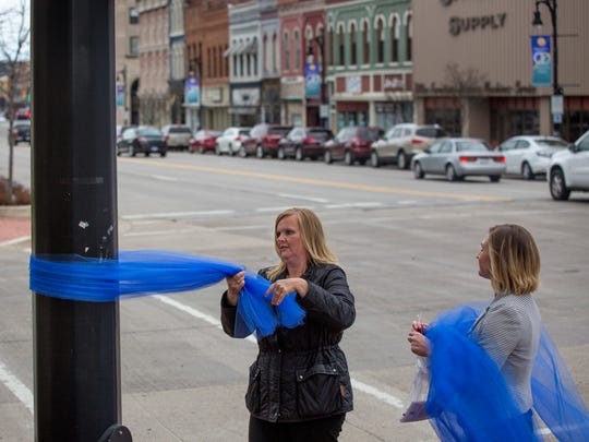 Shannon Pitts, left, and Lindsay Chopp, with the St. Clair County Child Abuse/Neglect Council, work on hanging blue ribbons on utility poles to promote awareness for National Child Abuse Prevention Month April 5, 2017 along Military Street in Port Huron.
