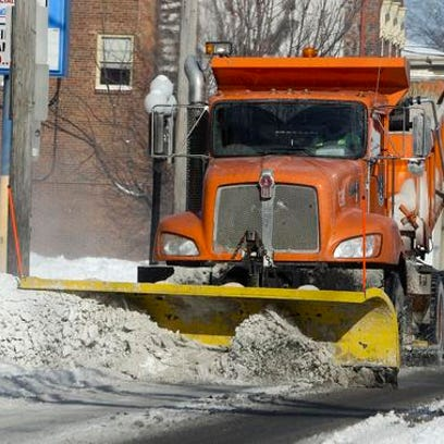 A snow plow prowls Baxter Avenue on Tuesday, February