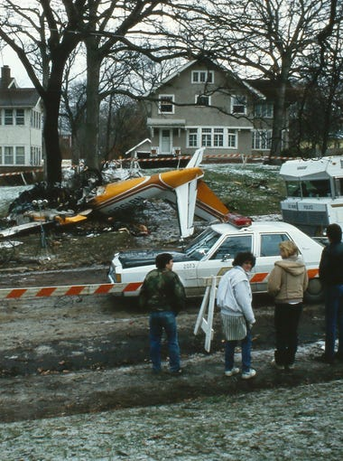 Wreckage of the small plane crash in a Des Moines neighborhood on Nov. 25, 1985, is viewed by onlookers the next day. The crash killed seven people, including members of the Iowa State women's cross country team.