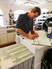 Richard Lamb works on score cards at Fort Myers Country