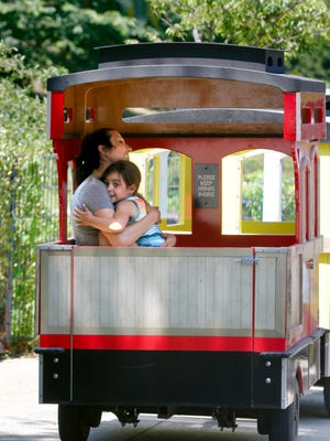 Five year old Emi Beranbe, of Providence, holds mom Justyna as they ride on the Carousel Express train around the carousel village Sunday afternoon.
