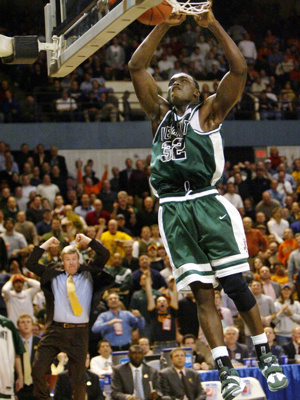 Vermont forward Germain Mopa Njila, right, throws down a dunk against Syracuse as coach Tom Brennan, left, celebrates on the sideline during the Catamounts' 2005 NCAA tournament victory