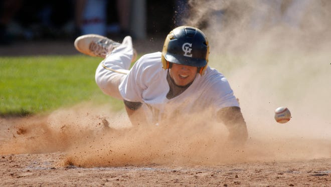 Grand Ledge's Brendan Baker slides in to score as the ball comes free from the Holt catcher Thursday, May 19, 2016, in Holt, Mich. Grand Ledge won 4-3 in the first game and 6-1 in the second.