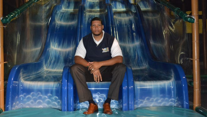 Robert Carter sits on the slide at the bottom of the 150-person jungle gym at Journey's Family Amusement Center. Carter gave up a good job with a major pharmaceutical company to return to his hometown of Fremont and open a business that would give back to the community.