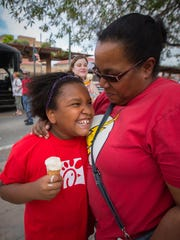 8-year-old Jasmine Mitchell is held by her mother Sherri Mitchell during the family-friendly event Kid's Night Out on Main St., June 11, 2016.
