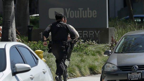 Officers run toward a YouTube office in San...