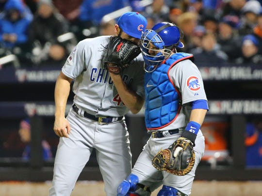 Chicago Cubs starting pitcher Jake Arrieta (49) talks with catcher Miguel Montero in the third inning against the New York Mets in game two of the NLCS at Citi Field