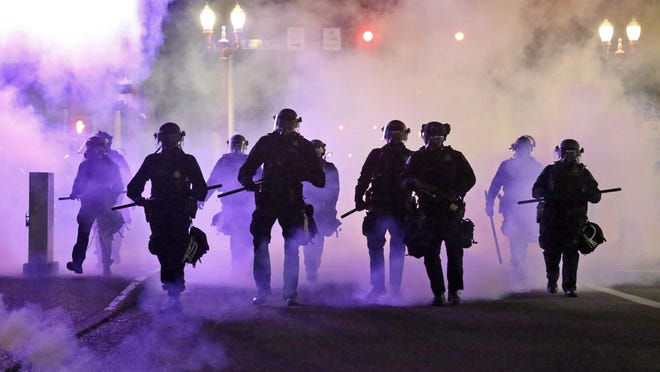 Police officers walk enveloped by tear gas in Portland on March 29.
