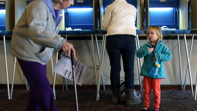 """Raegan Zilles puts on her """"I voted"""" sticker while her mom, Andi, casts her ballot for the presidential primary in 2016. The 2018 spring election will be April 3."""