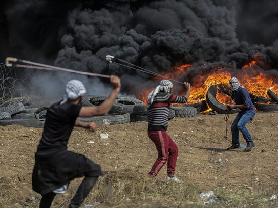 Palestinians protesters throw stones during clashes