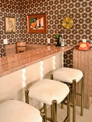 The built-in bar is decorated with brown and orange wallpaper in reference to a cool '70s vibe.