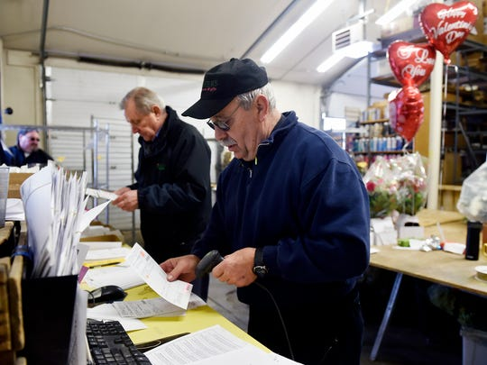 Jim Waughtel, center, checks order slips in the warehouse at Royer's Flowers & Gifts before going on a delivery run. Waughtel, who served 28 years as a York City firefighter, has spent the last three years of his retirement as a part-time delivery man for Royer's.