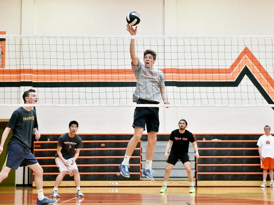 York Suburban's Ian Firestone, center, tips the ball during practice Thursday, April 7, 2016. The York Suburban boys volleyball team is off to a 2-0 start in the season.