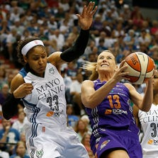 Mercury forward Penny Taylor (13) tries to push up to the basket against Minnesota Lynx forward Maya Moore (23) during the first half of Game 2 of the WNBA basketball Western Conference finals, Sunday, Aug. 31, 2014, in Minneapolis.