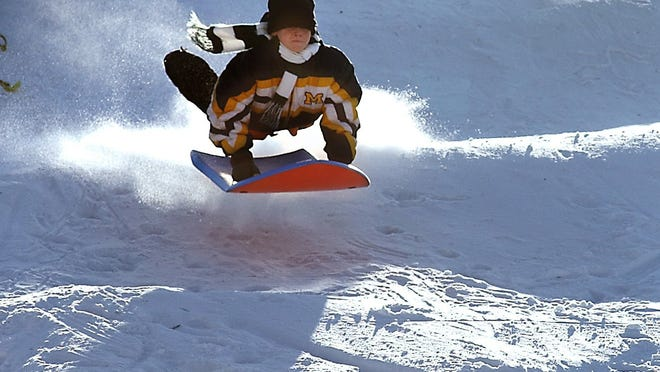 A youngster gets big air on the north slope of the sledding hill in East China Township Park on Recor Road.