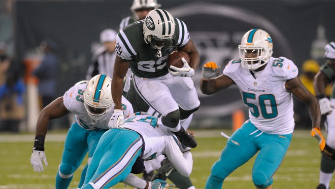 New York Jets running back Bilal Powell (29) is tripped up by the Miami Dolphins during the second quarter of an NFL football game, Saturday, Dec. 17, 2016, in East Rutherford, N.J.