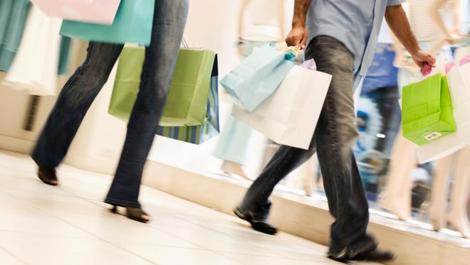 Couple shopping and carrying bags around a mall.