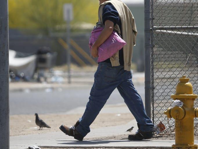 A homeless man walks to an encampment on the sidewalks