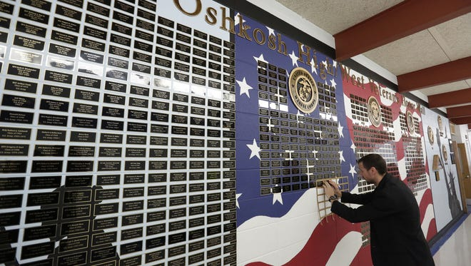 Andrew Schaler, a teacher at Oshkosh West High School and chairman of the Oshkosh High/West Veterans Honor Wall, puts a couple more names on the wall Wednesday, Nov. 8, 2017. The Oshkosh High/West Veteran Honor Wall is on display at Oshkosh West High School. It lists names of military veterans and current service members who attended Oshkosh High School or Oshkosh West High School. Organizers will continue to add names as veterans, their families and friends come forward.