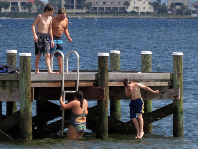 (l-r)  Sunday afternoon at the Shoreline Park South pier Bryce Williams, 13, Tanner Gwaltney, 10, Katelyn Gwaltney, 10, and Joshua Williams, 10, enjoy their last days of freedom before beginning a new school year by jumping off the park pier.