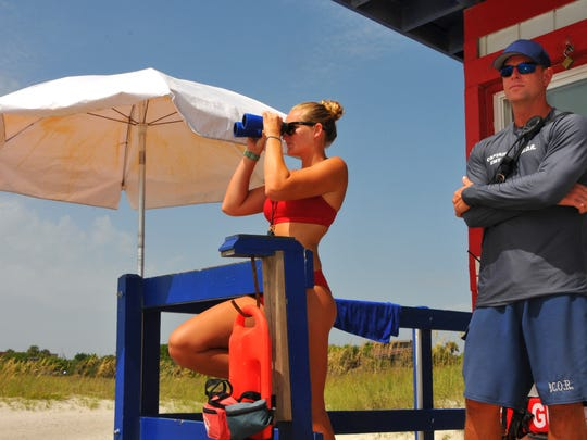 Brevard County Ocean Rescue lifeguard Mackenzie Broughton and Michael Curphey, lifeguard captain, keep an eye out for swimmers in trouble at Lori Wilson Park in Cocoa Beach in this 2015 photo.