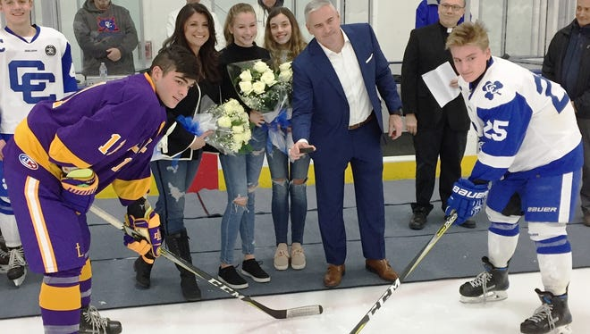 On hand for the cermonial puck drop for renaming at USA Hockey Arena for Mitchel Kiefer rink were family members Paula, Julianna, Alexa and Steven, along with DeLaSalle's Joseph Jenkins (11) and Catholic Central's Brendan West (25).