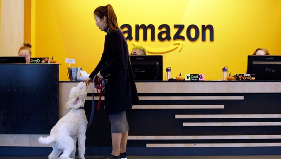An Amazon employee gives her dog a biscuit as the pair head into a company building, where dogs are welcome. Whichever city lands Amazon's second headquarters will be happy to have the tech giant in the neighborhood.