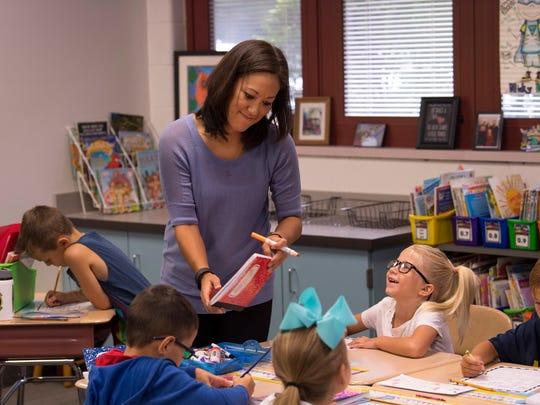 J.H. Castle first grade teacher Charlena Dan checks the work of student Charlotte Nanninga, second right, Monday morning.