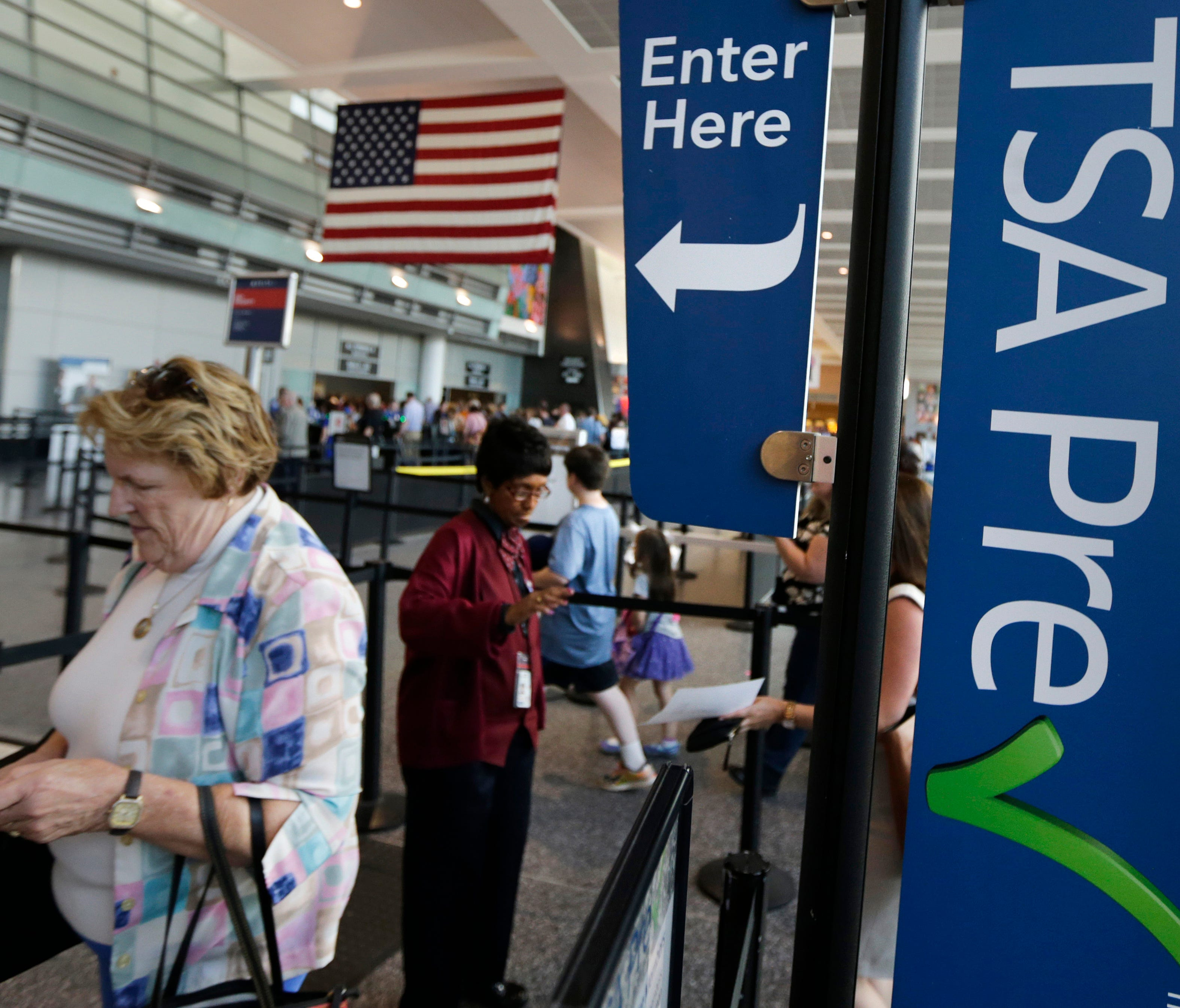 Travelers pass a sign for the Transportation Security Administration's TSA Precheck line as they walk to their departure gate in Terminal A at Logan International Airport on June 27, 2016.