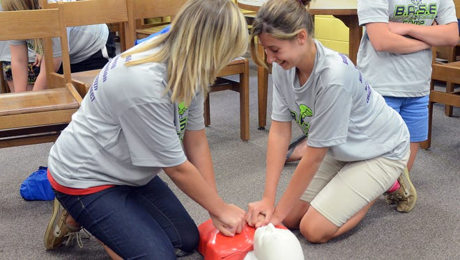Katie Burton, left, and Shelbie Salyers learn the proper way to give CPR on a mannequin at Boyle County High School in Danville, Ky.