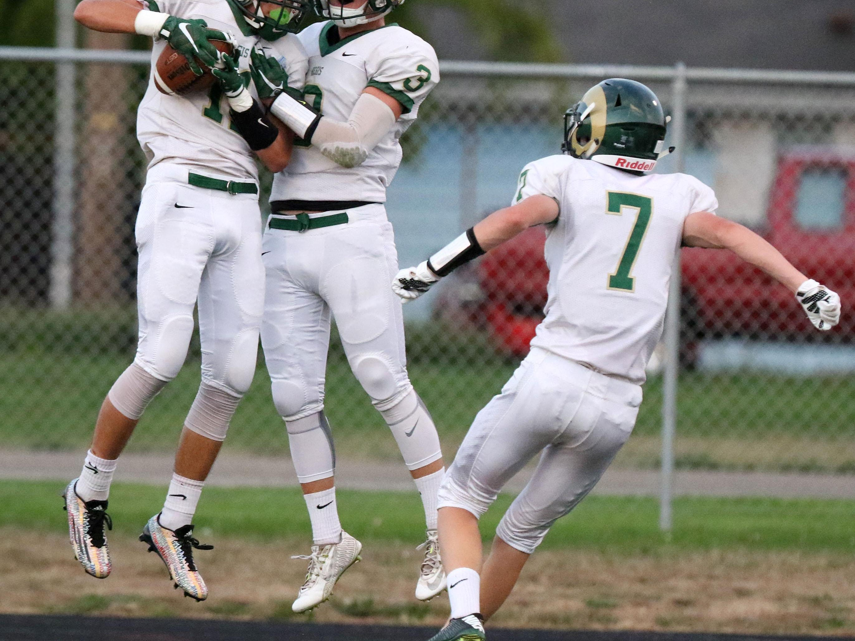 Regis junior Adam Wiltsey (11) celebrates his touchdown with teammate Austin Moore during their game with Dayton High School on Friday, Sept. 11, 2015, in Dayton, Ore.