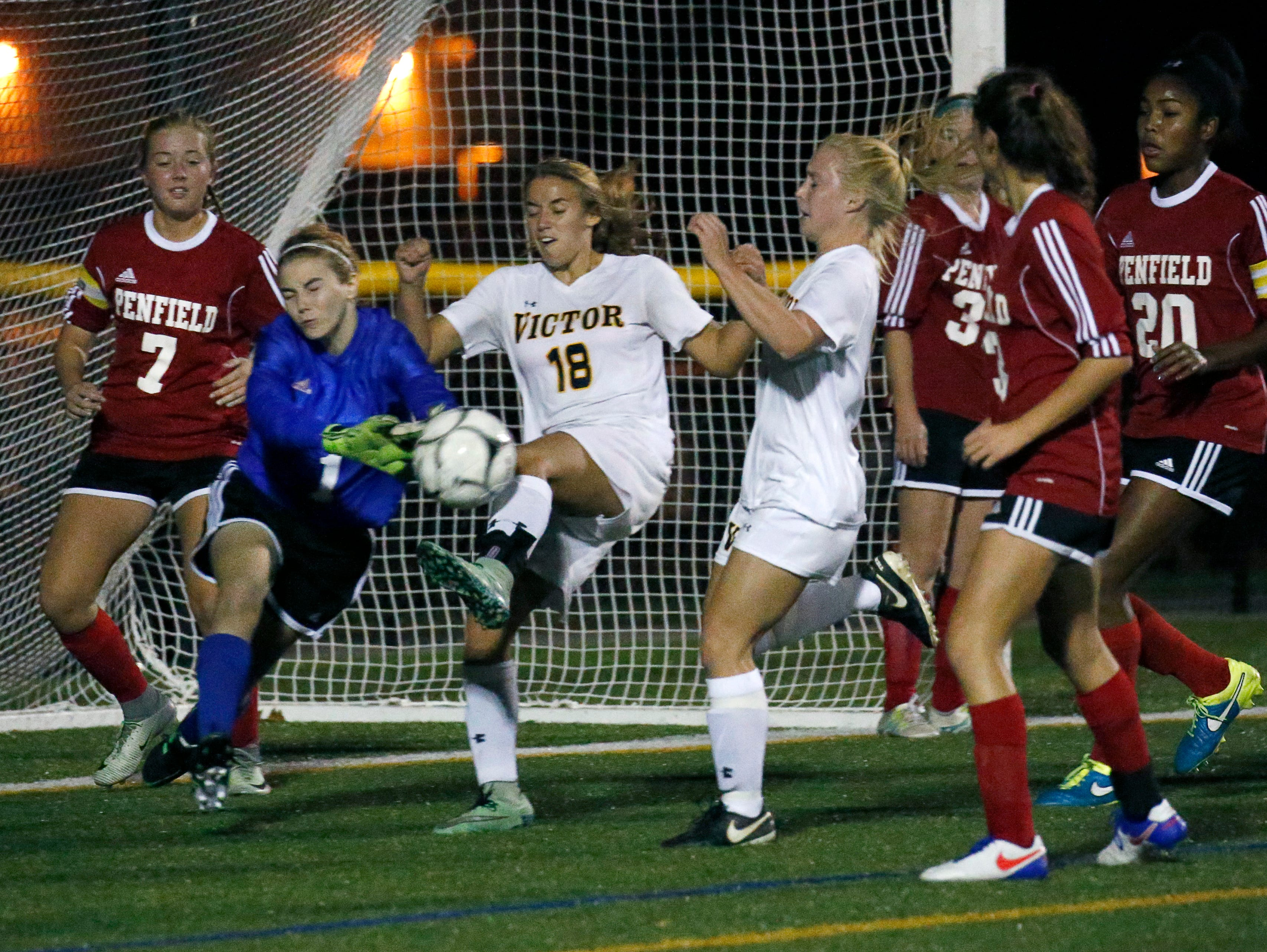A tense moment as Penfield goalie Jessica Pegg defends from Victor's Samantha White in the first half at Webster Schroeder High School.