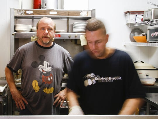 Tom Bohunsky, left, owner of the Rubber Biscuit Bar and Grill in Charlotte in the kitchen of his business. He said he isn't against food trucks, but believes officials shouldn't allow them into the city until downtown's vacant storefronts have been filled.