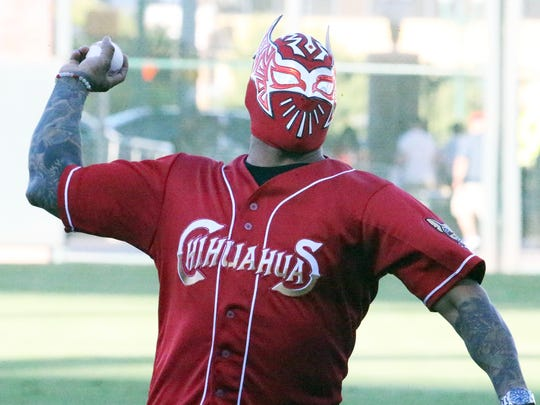 Sin Cara, a WWE wrestling character who is portrayed by a native El Pasoan, throws out the ceremonial first pitch before the start of a Triple-A playoff game between the El Paso Chihuahuas and the Oklahoma City Dodgers on Wednesday night at Southwest University Park. Sin Cara wears a mask completely covering his face. He was joined in throwing out the first pitch by Mike Guerrero, a disc jockey for The Fox-92.3 FM.
