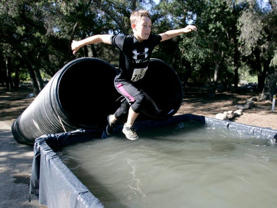 Randall Braziel takes the plunge in to a chilly tankful of water in the Krusher Mud Run in Santa Paula.