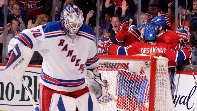Max Pacioretty of the Canadiens is mobbed by his teammates after scoring a second period goal at 3:44 as Rangers goaltender Henrik Lundqvist looks on during Game 5 of the Eastern Conference final.