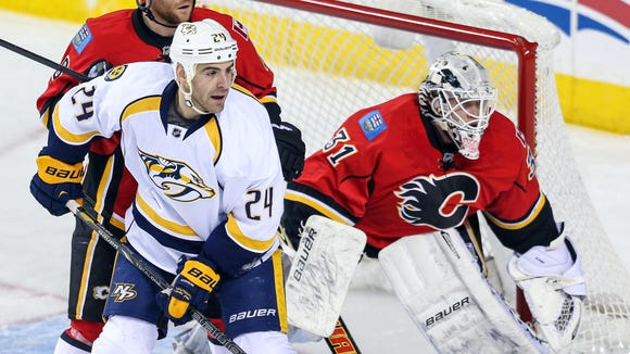 Nashville Predators left wing Eric Nystrom (24) and Calgary Flames defenseman Dennis Wideman (6) fight for position in front of goalie Karri Ramo (31) during the first period of a Jan. 24, 2014 game at Scotiabank Saddledome.