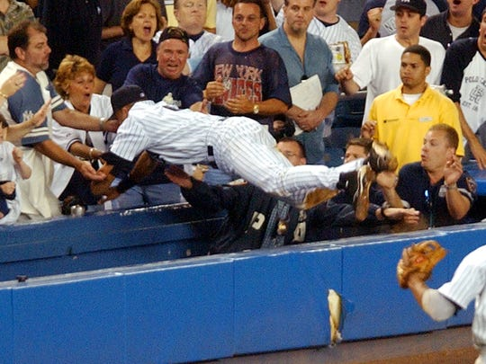 New York Yankees' Derek Jeter dives to catch a fly ball in the twelfth inning against the Boston Red Sox at New York's Yankee Stadium, Thursday, July 1, 2004. Jeter left the game and was injured on the play. The Yankees won the game, 5-4. (AP Photo/Frank Franklin II) ORG XMIT: NYFF114
