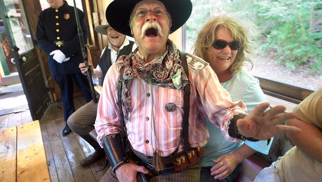 """Bob Alexander reacts after Karen Seibel places fake money into his shirt like a stripper while the """"bad guy"""" participates in a train robbery on Saturday. Alexander joined other outlaws and lawmen reenactors  for the monthly event hosted by Steam Into History."""