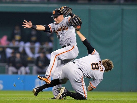 San Francisco Giants right fielder Hunter Pence bumps into second baseman Joe Panik after Panik caught a fly ball by Pittsburgh Pirates' Gaby Sanchez in the second inning of the NL wild-card playoff baseball game Wednesday in Pittsburgh.