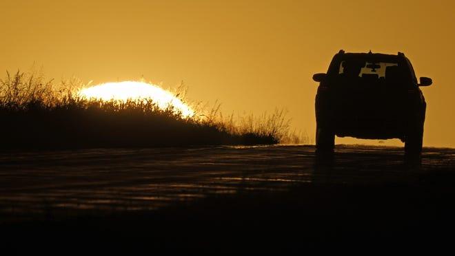 A motorist drives into the sunrise Thursday, Oct. 1, 2020, in Kansas City, Mo.