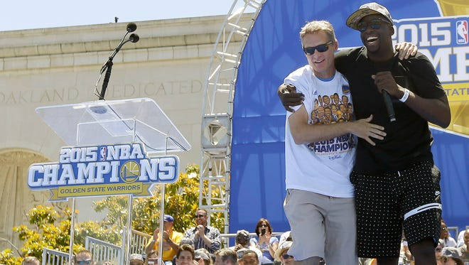 Golden State Warriors forward Draymond Green, right, brings head coach Steve Kerr to the front of the stage while speaking during a parade and rally for winning the NBA championship in Oakland, Calif., Friday, June 19, 2015.