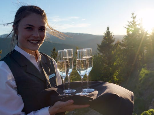 A server smiles while offering Enza prosecco from Deutsch