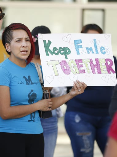 """Kristina Lopez holds a sign saying """"Keep Families Together"""" during a protest against the zero-tolerance immigration policy, that has led to children being separated from their parents at the border, outside the Sandra Day O'Connor Courthouse in Phoenix on June 18, 2018."""