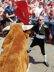 """Matador Eric Feazel bravely fights the bull before he was gored while taking a selfie in Dewey Beach. <137>as The 18th Annual Running of the Bull was held Saturday July 12th in Dewey Beach at the Starboard with a record crowd on hand to have the """"Bull"""" chase partier's down the beach and celebrate at the Restaurant and Bar with entertainment by Laura Lea & Tripp Fabulous.<137>"""