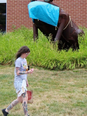 Courtney Dague of Akron walks past a frog sculpture -- which is outfitted in a mask to discourage the spread of coronavirus -- outside the Akron-Summit County Public Library branch at Highland Square on Wednesday, July 22, 2020.